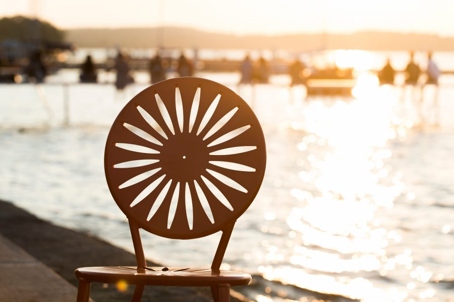 The sun sets over Lake Mendota and the cutout sunburst design of a silhouetted Memorial Union Terrace chair at the University of Wisconsin-Madison during a summer evening on July 26, 2014. (Photo by Jeff Miller/UW-Madison)